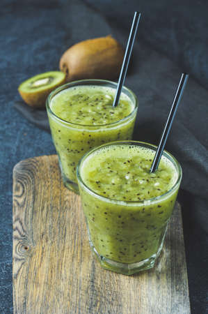 Fresh kiwi juice in glass over dark background. Diet concept, healthy eating or weight loss. Space for text, vertical cropping