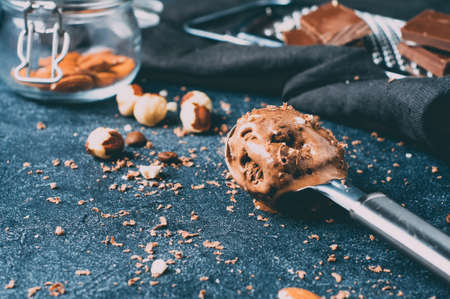 Chocolate ice cream on the spoon and ingredients over dark background concrete