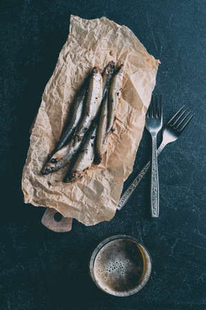Salted sprat on paper and beer over dark stone background. Vertical cropping
