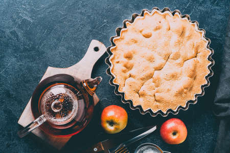 Apple pie, fresh apples and a pot of tea over dark concrete background