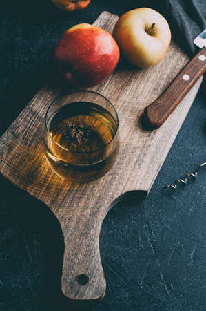Apple cider in a glass and fresh apples on dark stone background. Vertical cropping