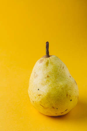 Ripe pear on a yellow background