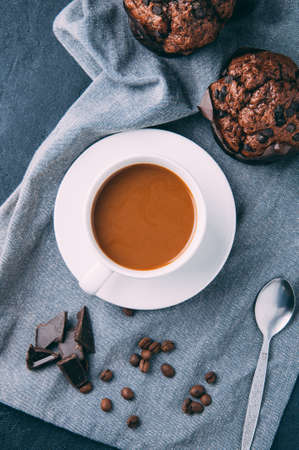 Chocolate muffins and coffee on a dark background