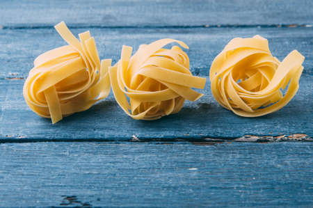 Raw uncooked pasta over blue background