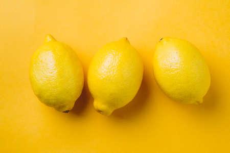 Lemons on yellow background Stok Fotoğraf
