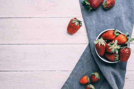 Ripe strawberries on white wooden background