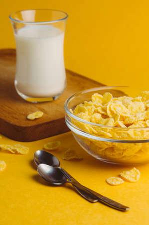 옥수수 부스러기와 우유는 노란색 배경입니다. 아침 컨셉