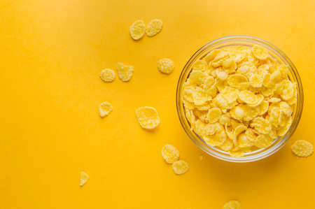 Corn flakes on a yellow background. Breakfast concept Stock Photo