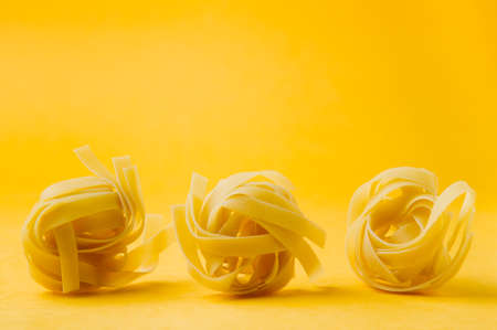 Raw uncooked pasta over yellow background