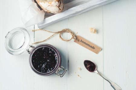 Eigengemaakte jam in een kruik en brood in een witte houten doos over witte houten achtergrond Stockfoto