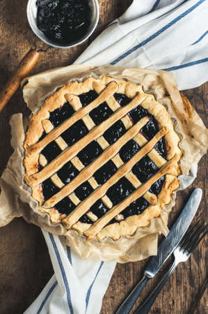 Pie with plums on the grill over the old wooden table Stock Photo