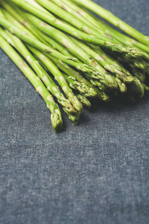 Fresh green asparagus over gray textile background