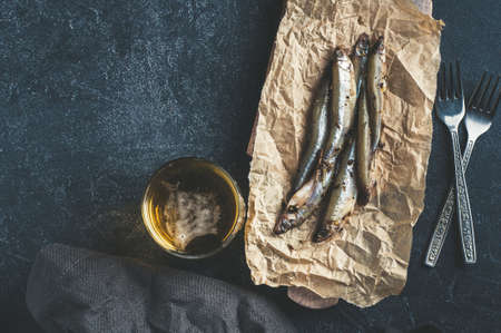 Salted sprat on paper and beer over dark stone background. Copy space for text or design Stock Photo