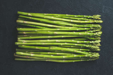 Fresh green asparagus on dark concrete background