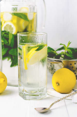 Water with lemon and peppermint in the glass on a bright background. Diet or weight loss concept