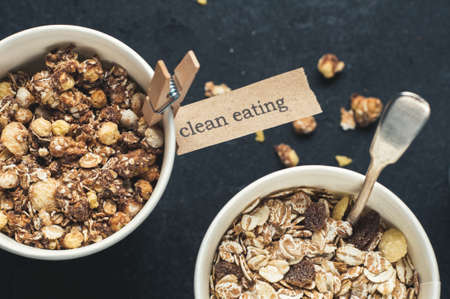 Breakfast cereals in paper cups over dark concrete background. Diet or healthy eating concept