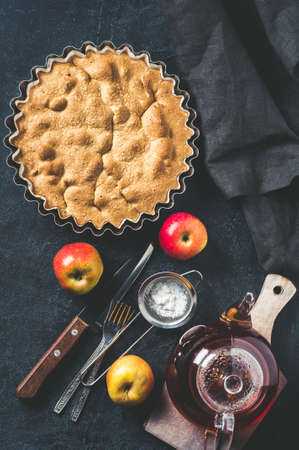 Apple pie and fresh apples on a dark wooden table