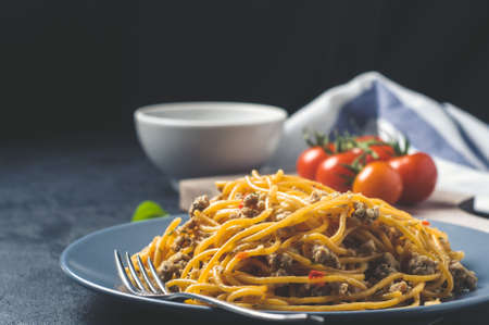 Spaghetti with tomatoes in a blue bowl over dark concrete background