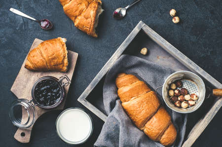 Fresh croissants with jam in a wooden box, jar of jam, a glass of milk, nuts over dark concrete background. Breakfast concept, top view
