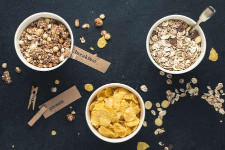 어두운 콘크리트 배경 위에 종이 컵에 아침 시리얼. 다이어트 또는 건강한 먹는 개념