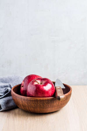 Red apples in a bowl on a light wooden background. Diet or healthy eating concept Stok Fotoğraf - 83063993