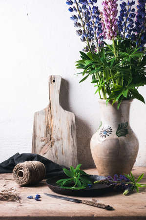 Bouquet of lupines in a clay jug on a wooden table. Concept of the village Stock Photo