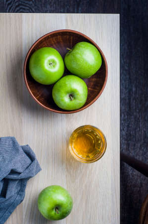 Green apples in a bowl on a light wooden background. Diet or healthy eating concept Stock Photo