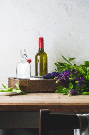 ルピナス、白いコンクリートの壁の背景に古い木製のテーブルに陶器の花束