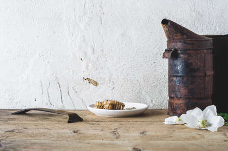 Flowers, smoker and tools on a wooden table against the background of a light wall. Concept of an apiary Stock Photo