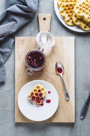 Homemade wafers and raspberry jam on a gray concrete background. Top view and flat lay