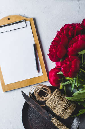 Bouquet of red peonies and tablet on a white concrete background