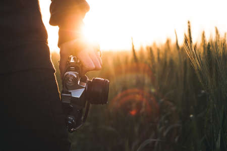 The woman with a retro camera against the background of a sunset in the wheat field