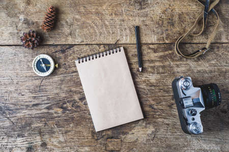 レトロなカメラと木製の背景にコンパス。旅行の概念