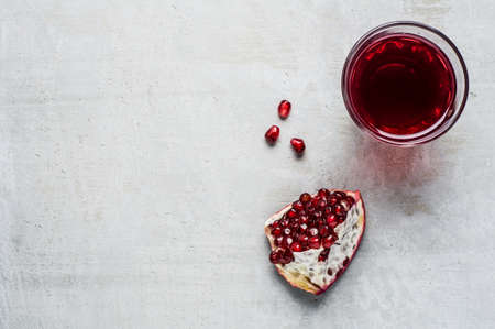 Red pomegranate and juice in a class on a grey concrete background