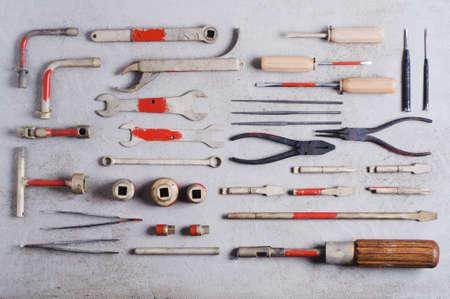 Een reeks oude hulpmiddelen voor de professionele werktuigkundige over grijze concrete achtergrond