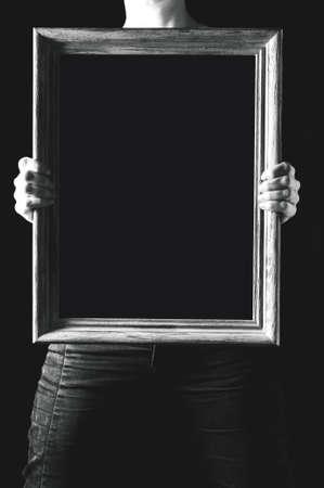 Tela nera nelle mani della donna. Il posto per il testo o il disegno su una tela Archivio Fotografico - 83100629