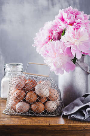 Concept of rural kitchen. Peonies in a can, flour and eggs on a wooden table against the background of a gray concrete wall