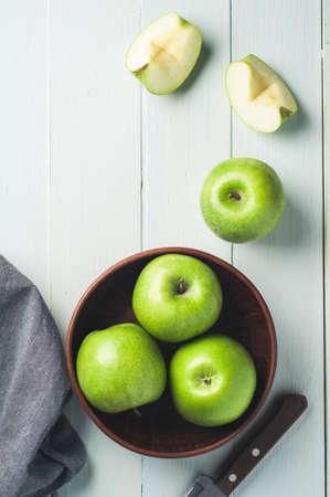 軽い木製の背景上にボウルに青りんご。ダイエットや健康的な食事の概念 写真素材