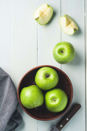 Green apples in a bowl on a light wooden background. Diet or healthy eating concept Stok Fotoğraf