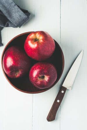 Rode appels in een kom op een lichte houten achtergrond. Dieet of gezond eten concept