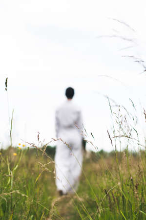 The woman in white clothes with a bouquet in her hand in the field of grass Stock fotó