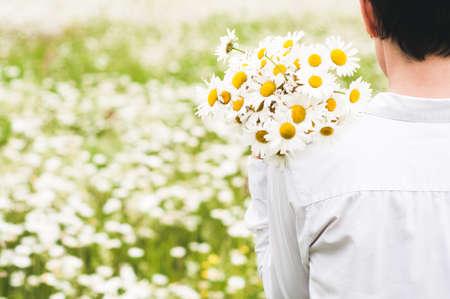 camomiles의 분야에서 그녀의 손에 꽃다발과 흰 옷을 입은 여자 스톡 콘텐츠