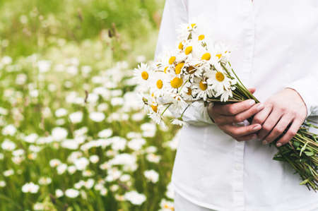The woman in white clothes with a bouquet in her hand in the field of camomiles Фото со стока - 83101325