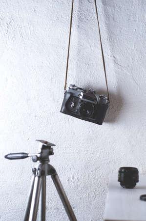 오래 된 카메라와 흰색 콘크리트 배경에 삼각대