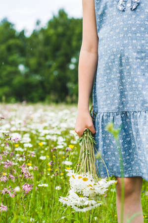 The girl in a blue dress holds a bouquet of white daisies in hand