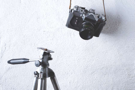 Old camera and tripod on a white concrete background Imagens - 83102002