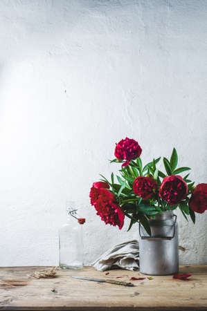 Bouquet of red peonies in a can on a wooden table against the background of a white wall Stock Photo