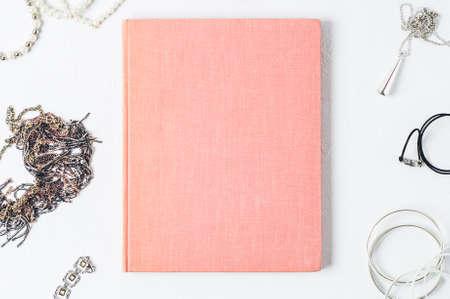 De juwelen van modieuze vrouwen en roze boek op een witte concrete achtergrond