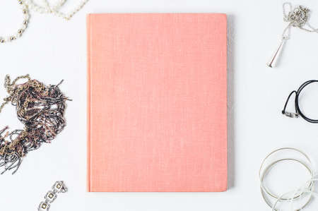 Fashionable womens jewelry and pink book on a white concrete background Imagens