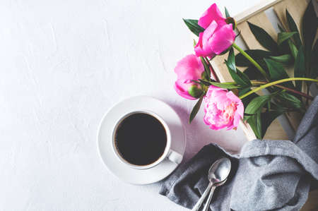 Pink peonies and  white cup of coffee  on a white concrete background. Breakfast or morning concept